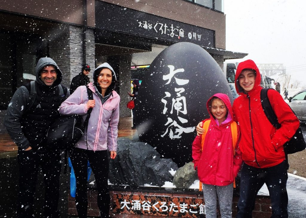 Posing by the black egg statue in Owakudani Valley on a day trip to Hakone - Passports and Spice